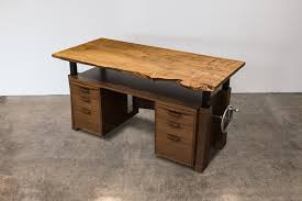 solid wood executive desk with adjule hand crank in standing position