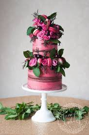 Pretty pink naked cake with cherries macarons and roses by.
