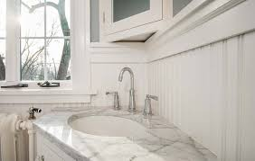 corner vanity with white marble countertop wide spread faucet in 1920 craftsman bathroom remodel in