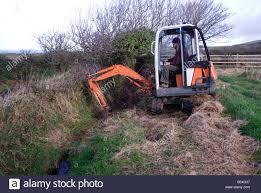 Simon Buttimore cavando zanjas con una mini excavadora en la Isla de Man  Fotografía de stock - Alamy