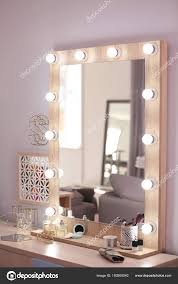 Mirror With Light Bulbs And Cosmetic Products On Dressing