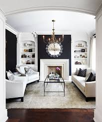 beautiful living room with black walls white fireplace built ins and crown molding