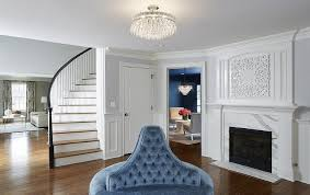 joe nye trillion flush mount illuminating a round blue velvet tufted bench with backrests facing a white fireplace mantle lined with a calacatta marble