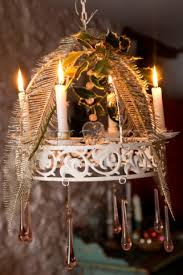 white chandelier with lit candles dressed for with silvered feathers holly and glass drops