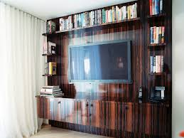 interior large dark brown varnished wooden cabinet with rectangular tv in middle plus brown wooden