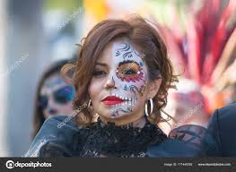 woman with sugar skull makeup during day of the dead stock photo