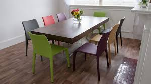 wooden dining table and multi coloured dining chairs