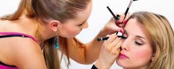 a makeup artist focusing on her customer s eyes