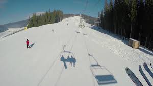 ski lift moving up the mountain with snow covered ski trails skiers and snowboarders