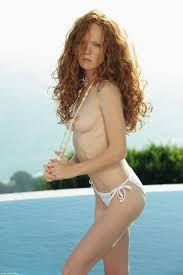 Flirtatious red haired chick Heather Carolin poses topless by the.