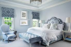Blue master bedroom features a blue print bed dressed in white and blue  bedding as well as blue trellis pillows flanked by open gray bedside tables  and ...