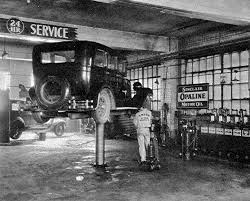 a lube rack in an unknown garage which is serving up pennsylvania sinclair opaline motor oil on the far right of the photo are the oil dispensers with