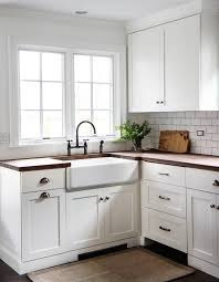 white shaker kitchen cabinets with wood countertops and farmhouse sink