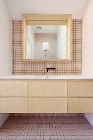 australian designer dan fer outfitted a family bath in pale pink tiles light wood