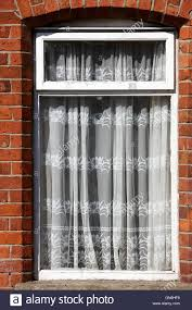 old net curtains hanging in the window of a red brick victorian terraced house