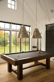 game room features a paneled cathedral ceiling lined with two goodman hanging lamps suspended over a pool table