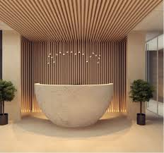round concrete reception desk timber cladding runs from wall to ceiling love the muted colours and the harmonious use of concrete and wood