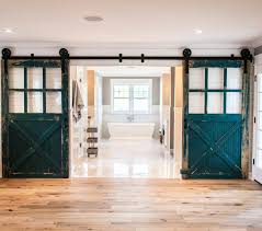 with wide planked hardwood floors alongside shiplap clad walls framing doorway highlighted by pair of peacock blue sliding barn doors with glass panes