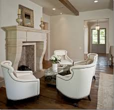 amazing living room with white nailhead trim accent chairs surrounding limestone fireplace herringbone firebox set of antique mirrored cube accent tables