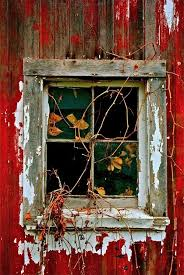 old barn window with weathered red paint