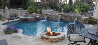 Patio with pool Modern Large Custom Sweetwater Stone Patio With Matching Large Sweetwater Ledger Stone Water Wall With Two Lava Rock Fire Pits The Backyard Also Encompasses An Stately Scapes Entertainment Pool And Spa Patio Gemini Landscape Construction
