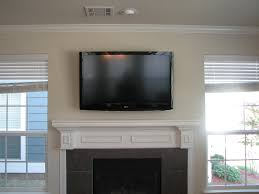 mount tv over fireplace. Wall Mounted TV Over Dark Grey Stone Fireplace With White Mantel Shelf Between Two Window On Ivory Theme Mount Tv