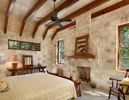 rustic modern bedroom with exposed wooden beams and stone and mortar wall design northworks