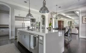 white kitchen cabinets black granite countertops waterfall island brown ceramic floor tile plain light blue wooden kitchen counter sleek black granite