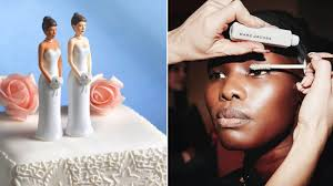 a wedding cake with two brides on top and a blue background closeup shot of a