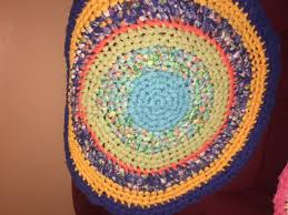beautiful round rag rug it has turquoise green orange blues and yellow 30 inch round made from cotton material