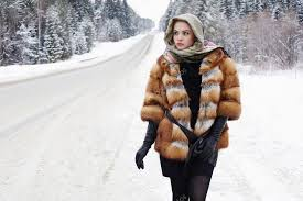 beautiful girl in a fur coat waiting for the car on a winter road in the