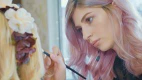 young makeup artist applying cosmetics on model s eyes royalty free stock image