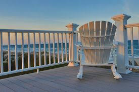 Adirondack chairs on beach sunset Wall Art Empty Adirondack Chair On Deck Balcony Overlooking The Beach And The Ocean At Sunset Adirondack Chairs Photos And Images Page Crystalgraphics
