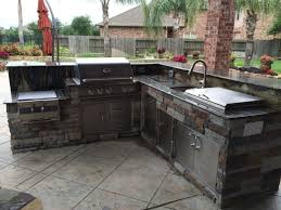 l shaped outdoor grill grey brick l shaped outdoor kitchen glass front upper cabinet green rustic wood chairs white drop in sink exterior glass door