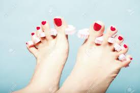 足のペディキュア ピンクつま先セパレーター青い背景の赤い爪で女の足を適用します