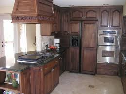 dark kitchens with oak cabinets and carved cooker hood over stove having microwave storage cupboard