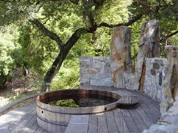 this rustic deck is a great example of how well a stone wall match a redwood