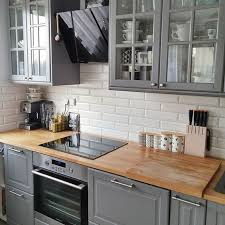 a kitchen with grey kitchen cabinets in wooden countertop and white tile backsplash