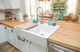 small country kitchen with white cabinets butcher block counters and double sided farmhouse sink