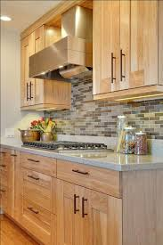 Light Colored Kitchen Cabinets With A Earth Tone Backsplash And A Grey  Quartz Counter