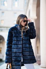 pam hetlinger wearing a winter chic outfit navy faux fur coat white jeans