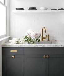Dark gray kitchen cabinets accented with aged brass knobs, vintage brass  inset pulls, and