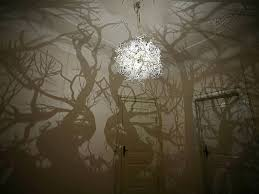 a collection of chandeliers entitled forms in nature by denmark based design group hilden diaz that casts shadows of trees on the surrounding walls