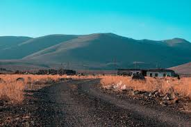 dry grass field background. Gray Road In Between Brown Grass Field With Mountains Background Dry