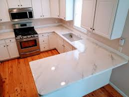 white countertops look like carrara marble on white cabinets with wood floor