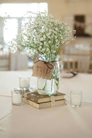 Simple, rustic centerpiece using old books, mason jar vases, Baby's Breath,  and