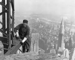 new york city a man working on a steel girder high about a city skyline