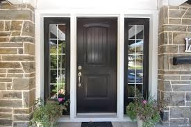 front door hardware black. large paned windows frame a matte black door with simple hardware on this stone brick home front