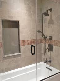 bathroom rectangle white bathtub and beige tile wall completed by glass door with black metal