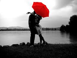 A Couple embraces under a red umbrella.